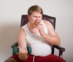 わざわざ筋トレをするためにドーナツを食べる太った男性
