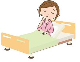 入院中のベッドでため息をつく女性患者