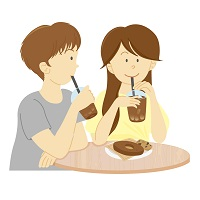 カフェでコーヒーを飲みながらドーナツを食べる若いカップル